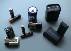 Various cells and batteries (top-left to bottom-right): two AA, one D, one handheld ham radio battery, two 9-volt (PP3), two AAA, one C, one camcorder battery, one cordless phone battery